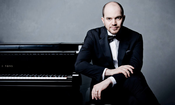 Kirill Gerstein sitting next to piano