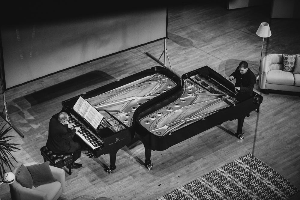 two gentleman playing the piano on stage in black and white