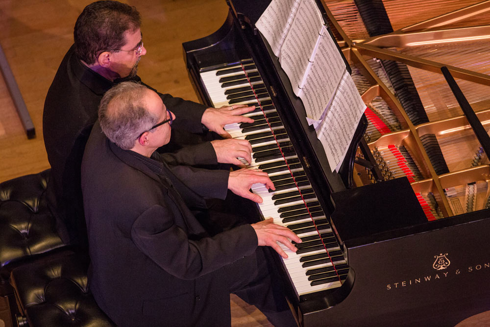 two gentleman playing the piano on stage