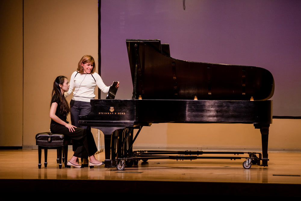 lori sims helping student on piano