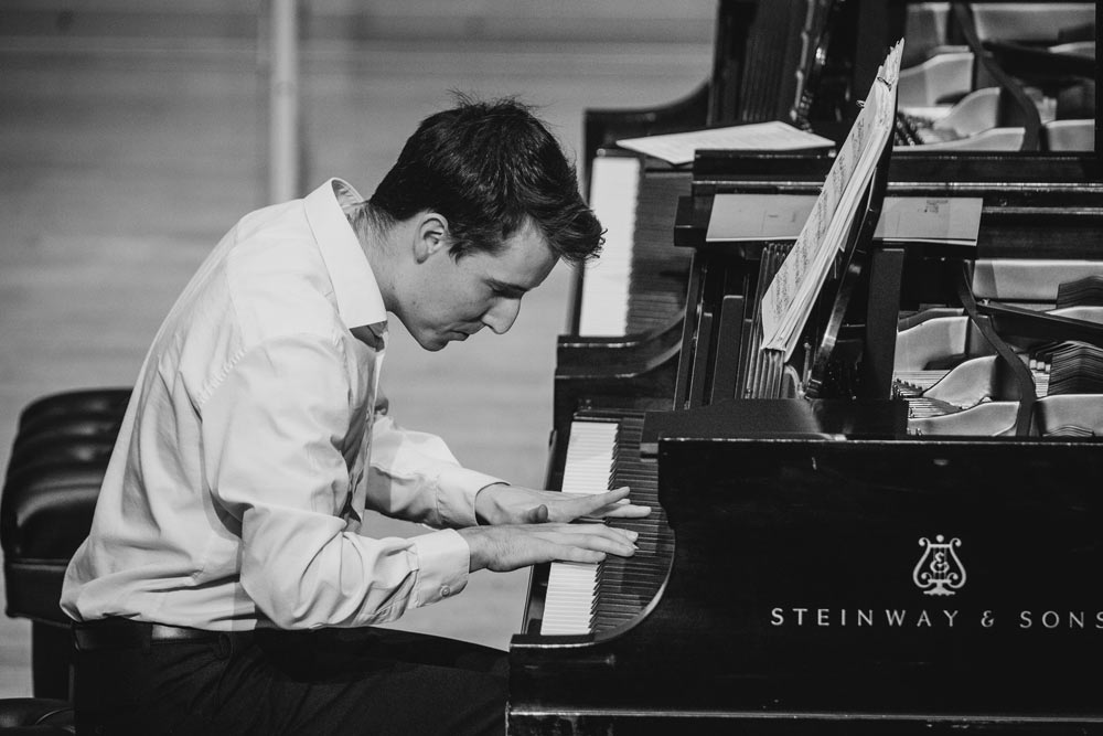 gentleman playing the piano on stage in black and white