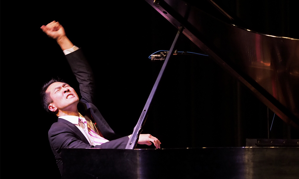 gentleman playing piano with his arm in the air