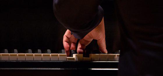 gentleman pressing keys on a piano