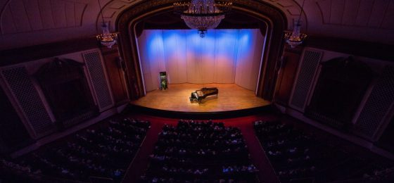 gentleman playing piano on stage in front of audience
