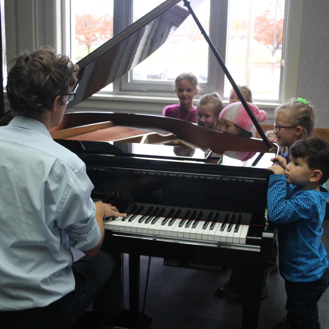 teacher teaching students how to play piano