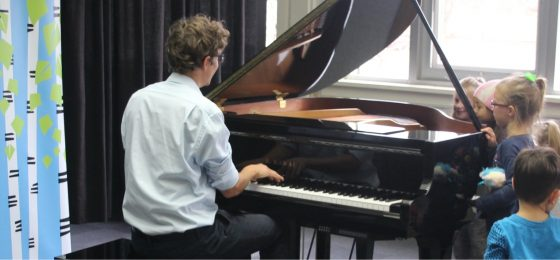 teacher playing the piano for little kids