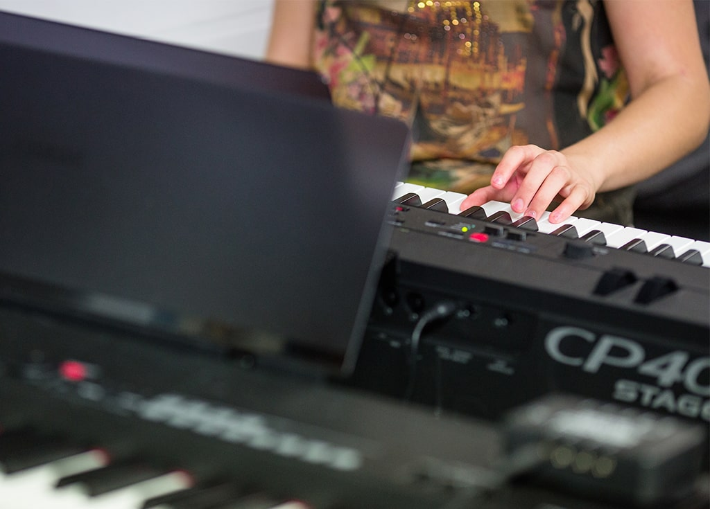multiple keyboards are visible and one woman's hand plays