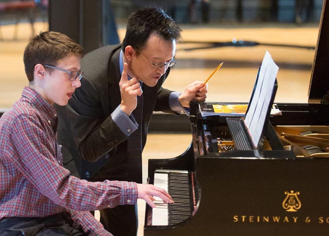 teacher helping student on piano