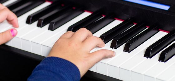 a girl with pink nail polish plays the piano