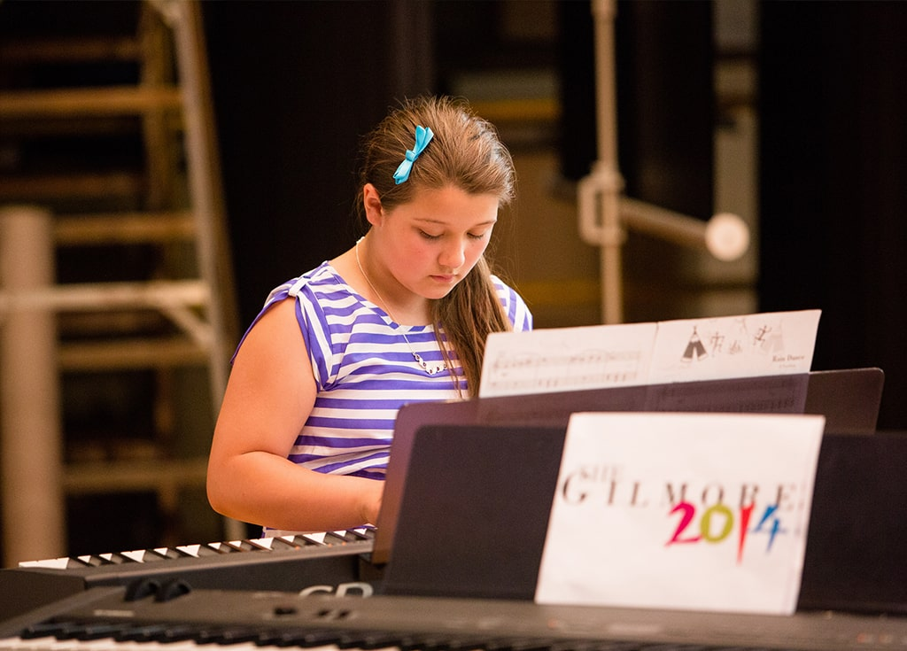 a girl looks down at her hands while playing the keyboard