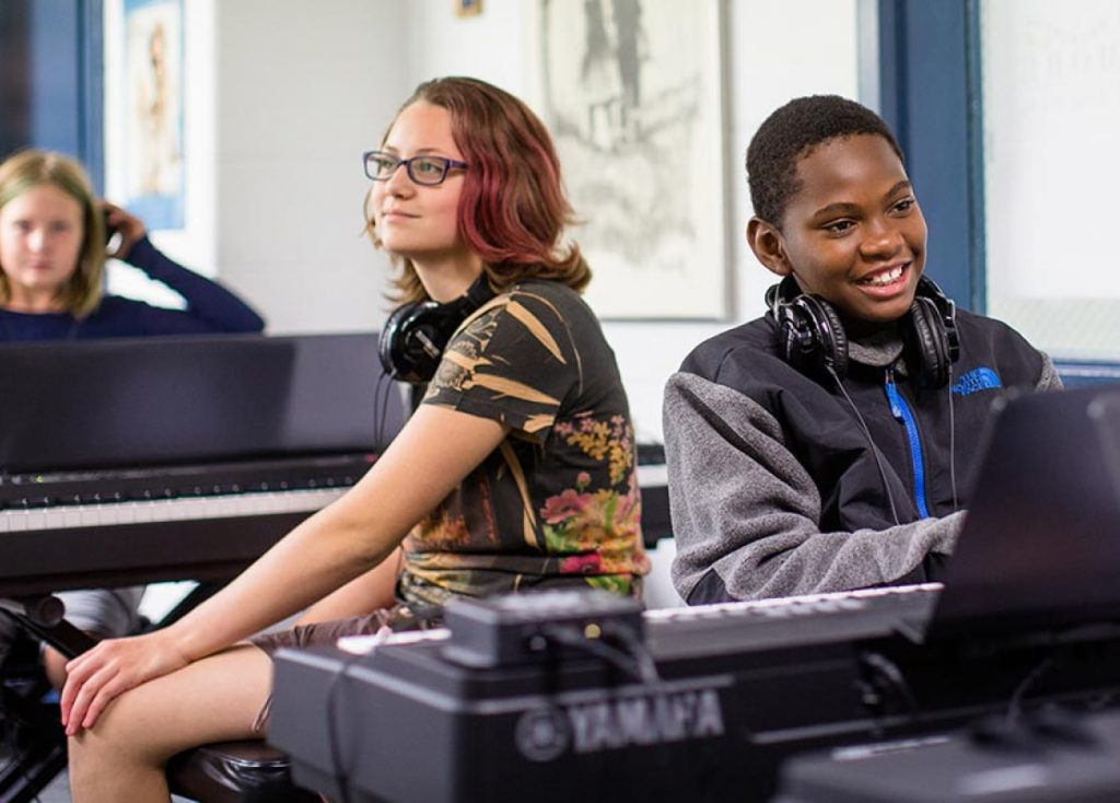 two students learning about music education