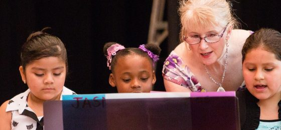 woman plays piano with three children at the gilmore piano lab recital