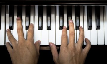 hands play a piano overhead angle