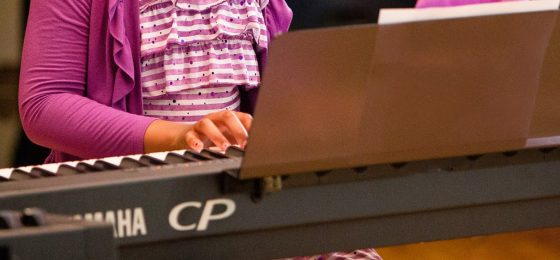 close up of a keyboard and hands of a girl playing it