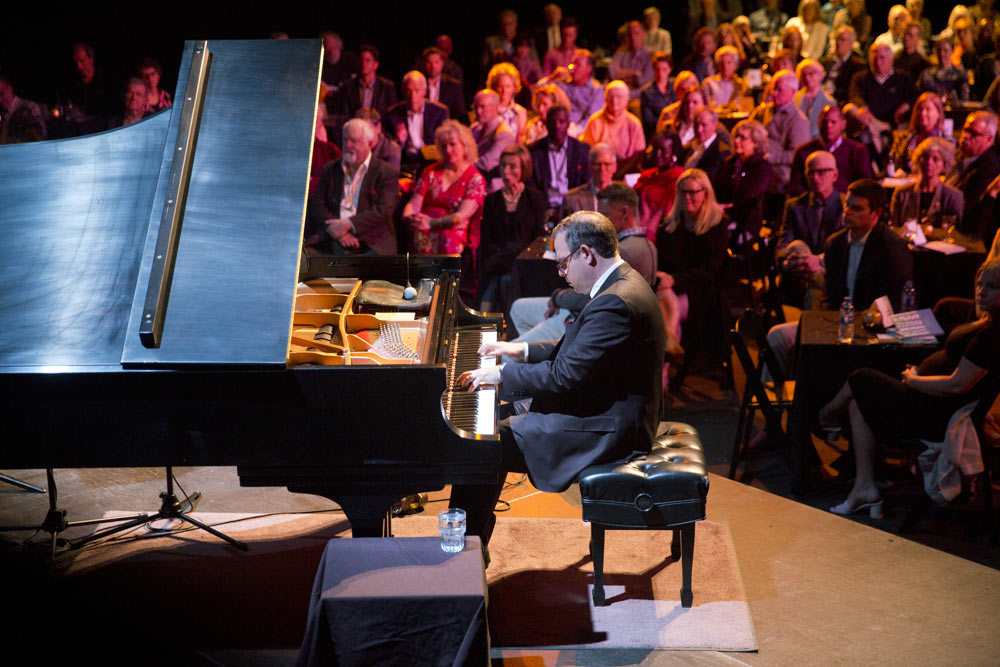 close up of gentleman playing piano on stage