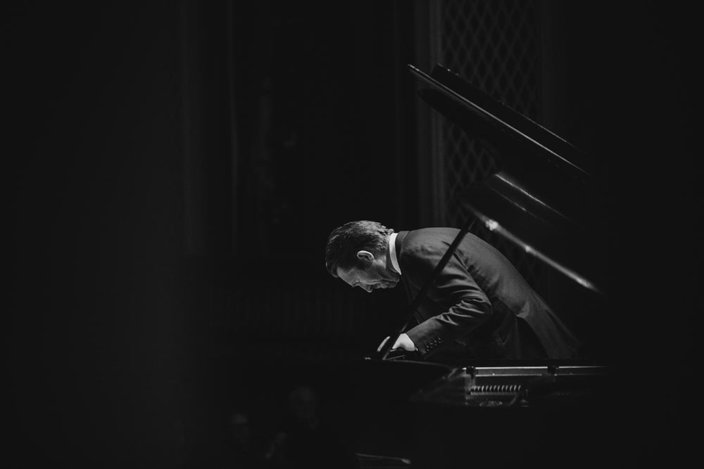 Leif Ove Andsnes taking a bow on stage in black and white