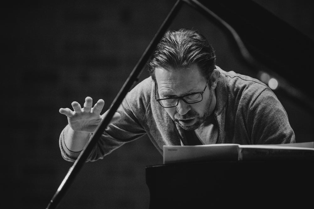 close up of Leif Ove Andsnes looking at music notes in black and white