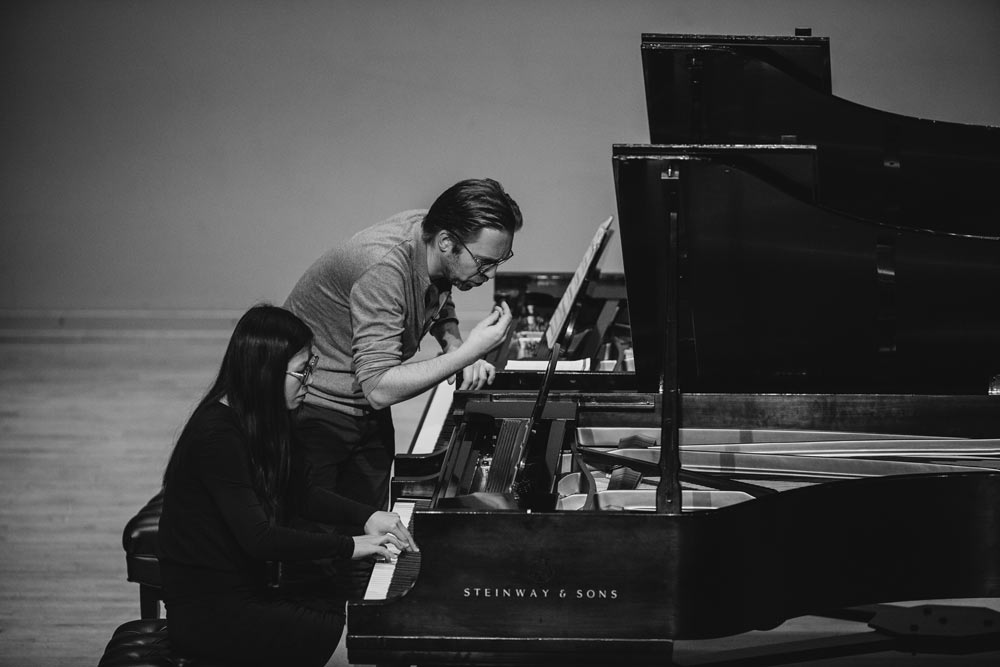 Leif Ove Andsnes teaching a woman how to play the piano in black and white