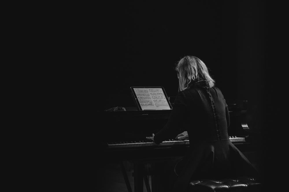 back view of a woman playing the piano