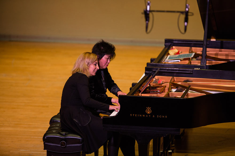 Katherine Chi and her friend playing the piano on stage at Dalton Center.