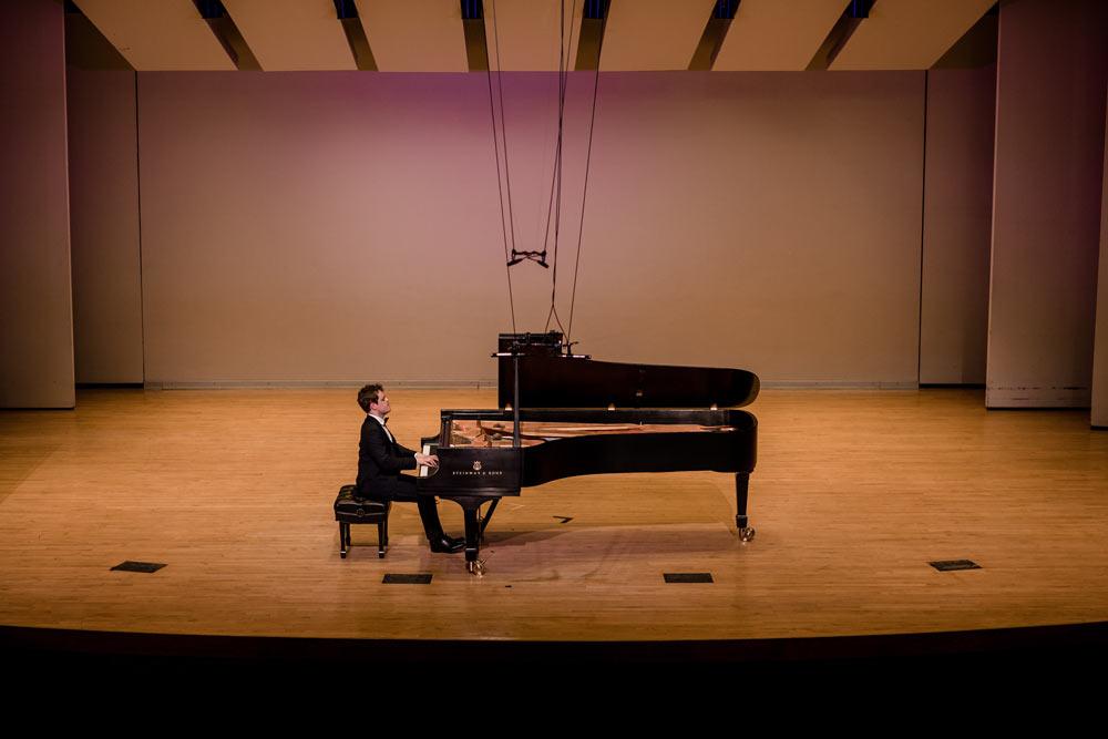 Benjamin Grosvenor playing piano on stage