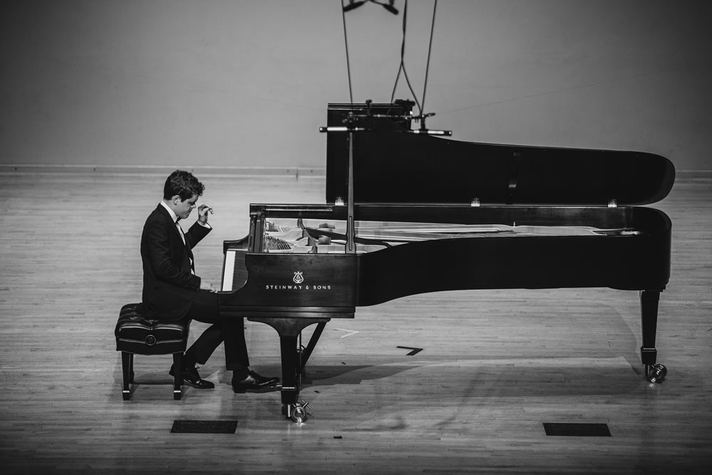 Benjamin Grosvenor playing piano on stage in black and white