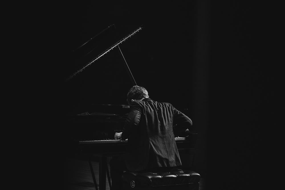 Benjamin Grosvenor playing the piano on stage in black and white