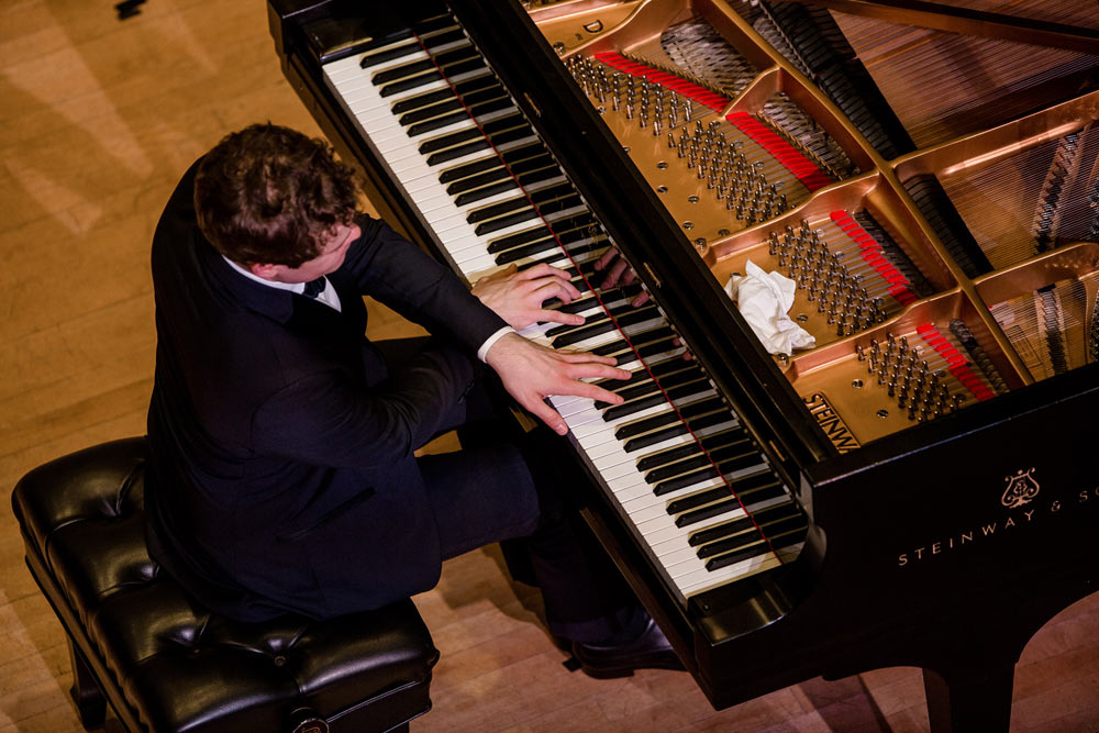 Benjamin Grosvenor playing the piano on stage