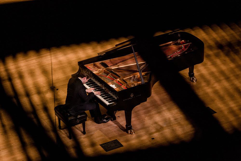 side view of Benjamin Grosvenor playing the piano on stage