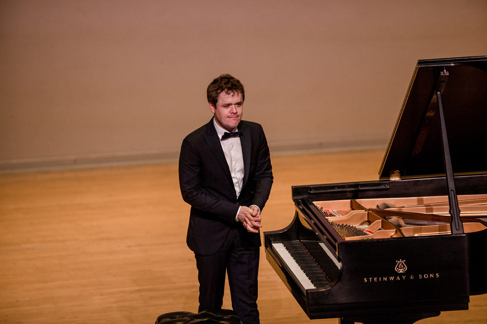 Benjamin Grosvenor standing on stage smiling