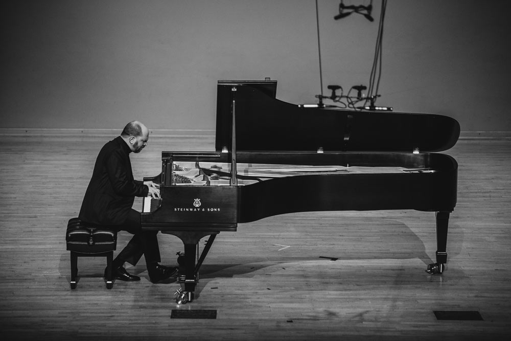 Kirill Gerstein playing the piano on stage in black and white