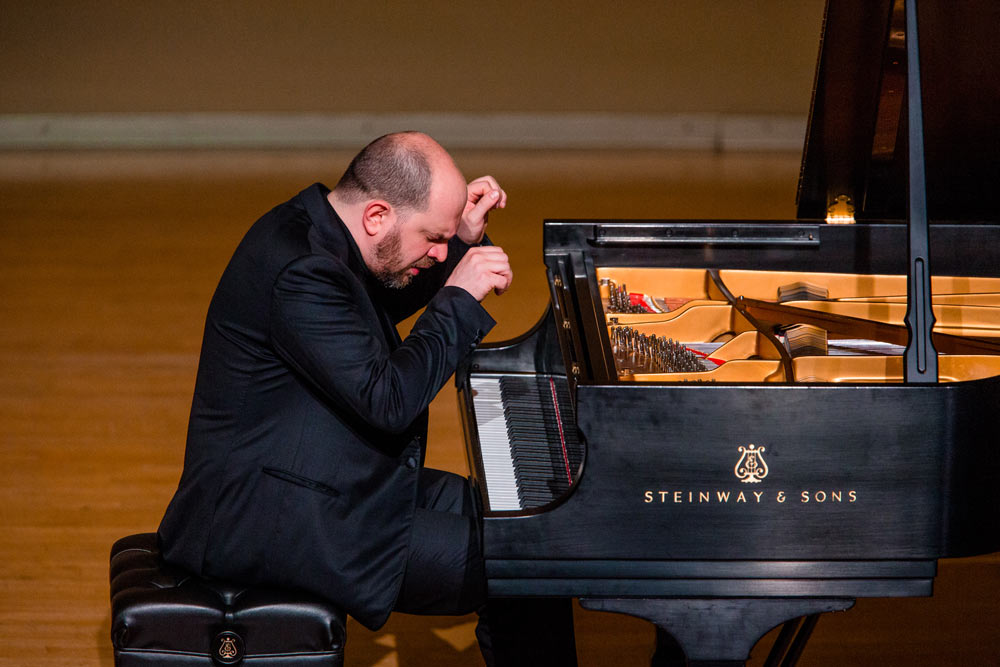 Kirill Gerstein playing the piano on stage