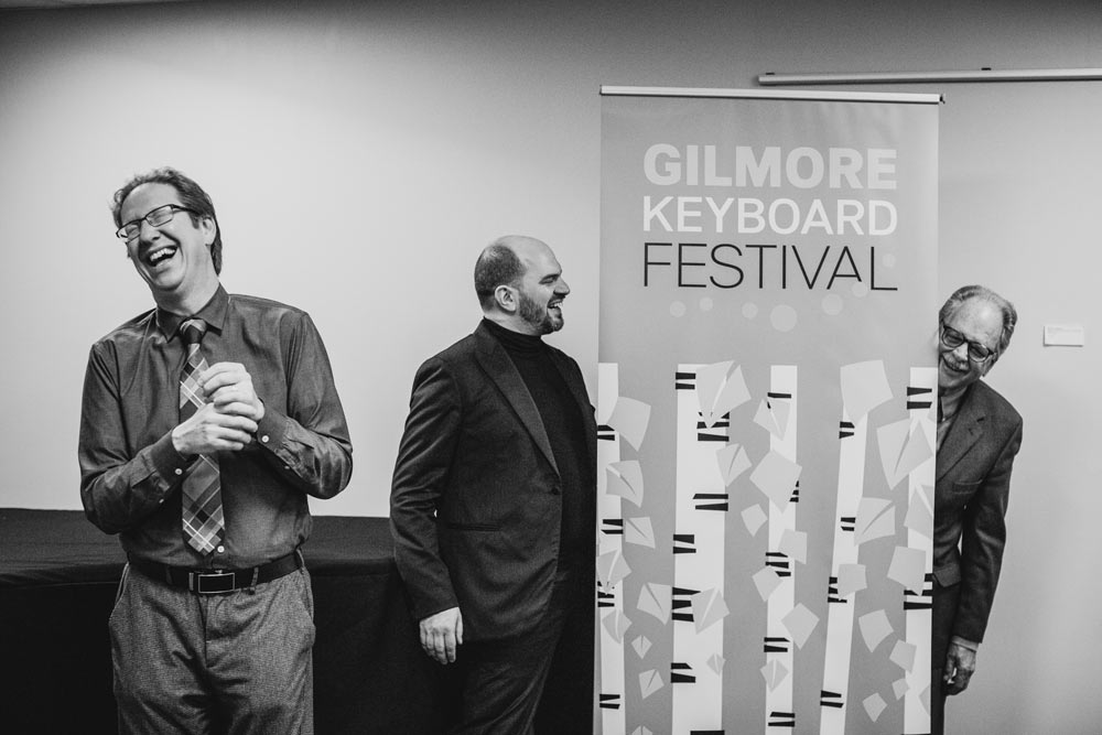 Kirill Gerstein standing next to Gilmore Keyboard Festival sign in black and white