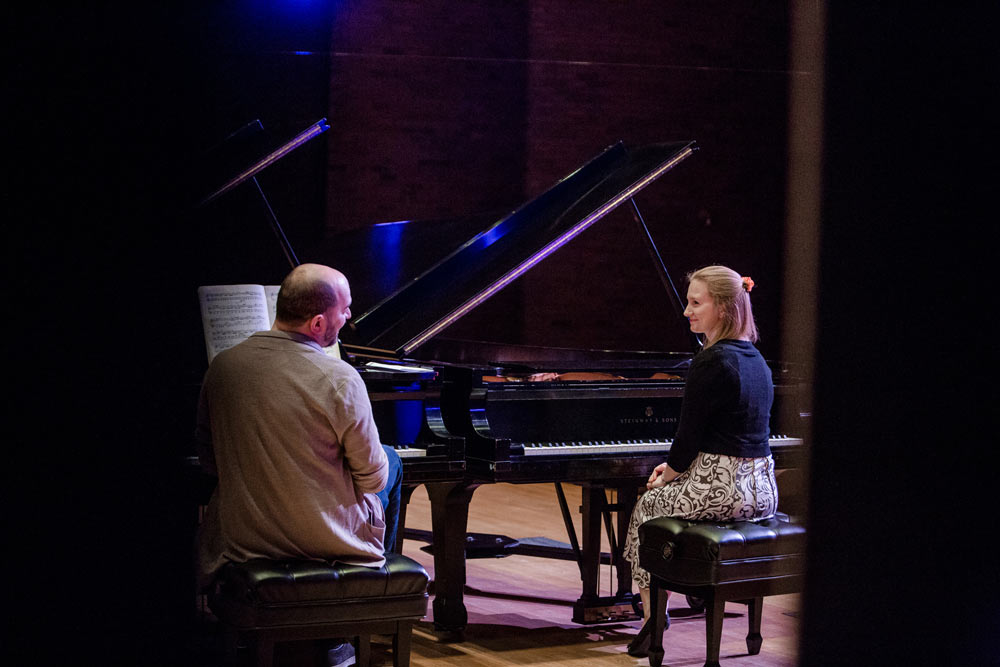 Kirill Gerstein on stage with a woman playing the piano