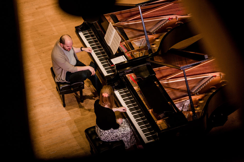 Kirill Gerstein and a woman playing the piano on stage