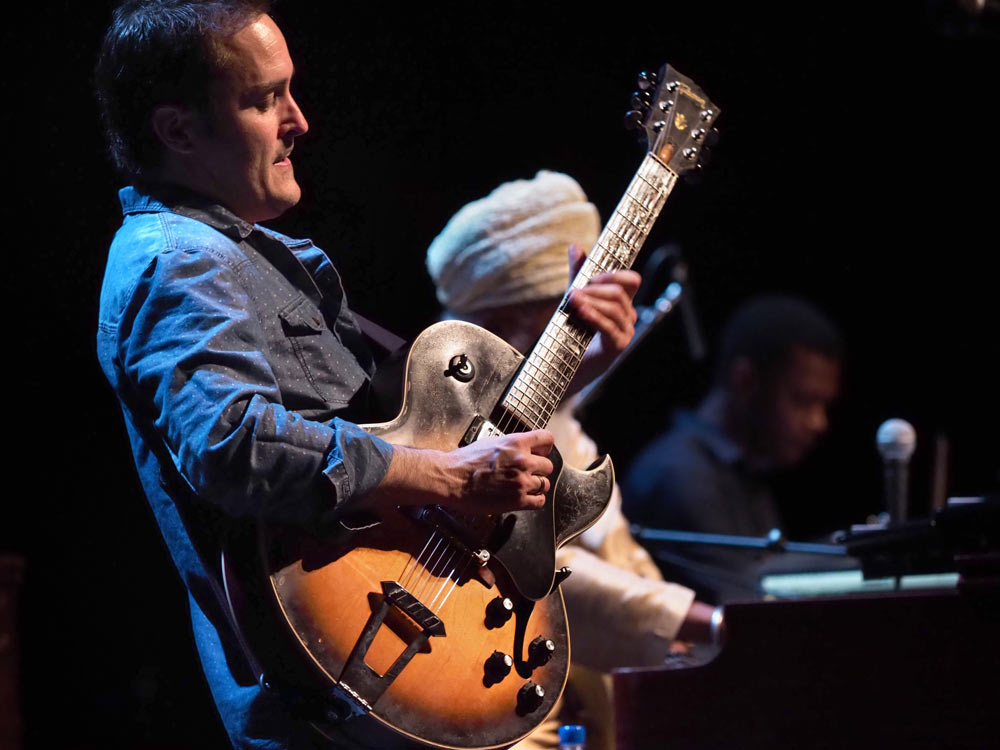 close up of gentleman playing guitar on stage