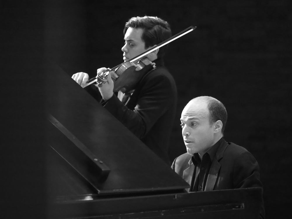 Benjamin Beilman & Orion Weiss playing instruments in black and white