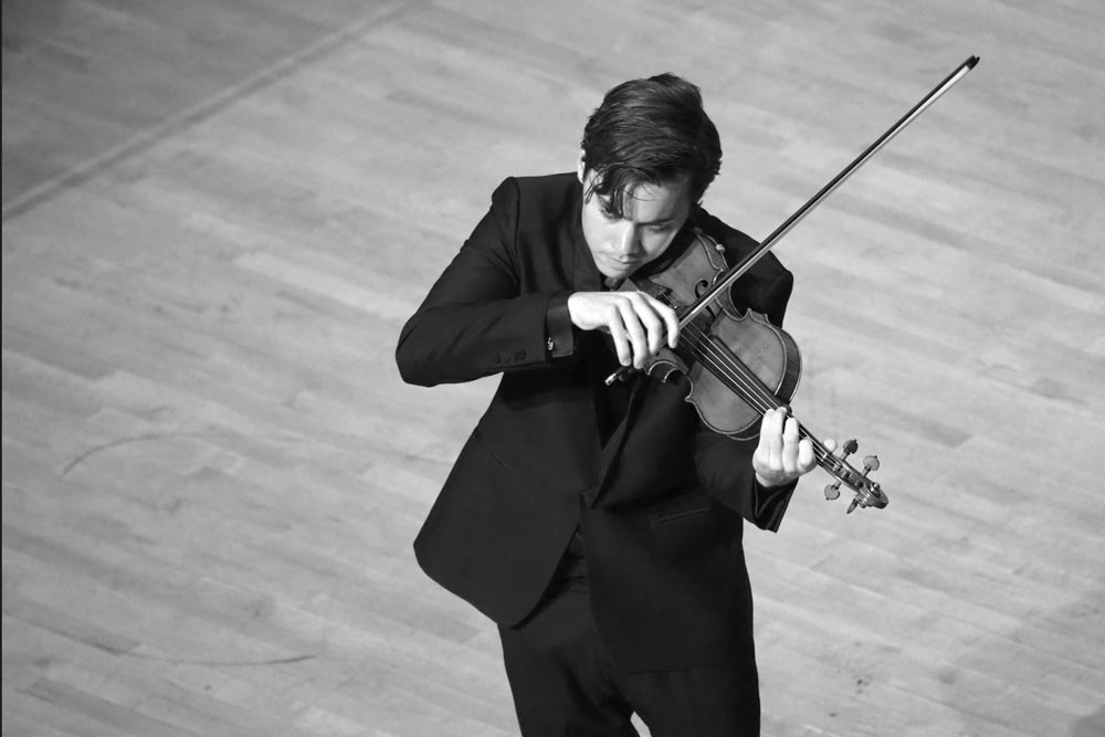 Benjamin Beilman playing violin on stage in black and white