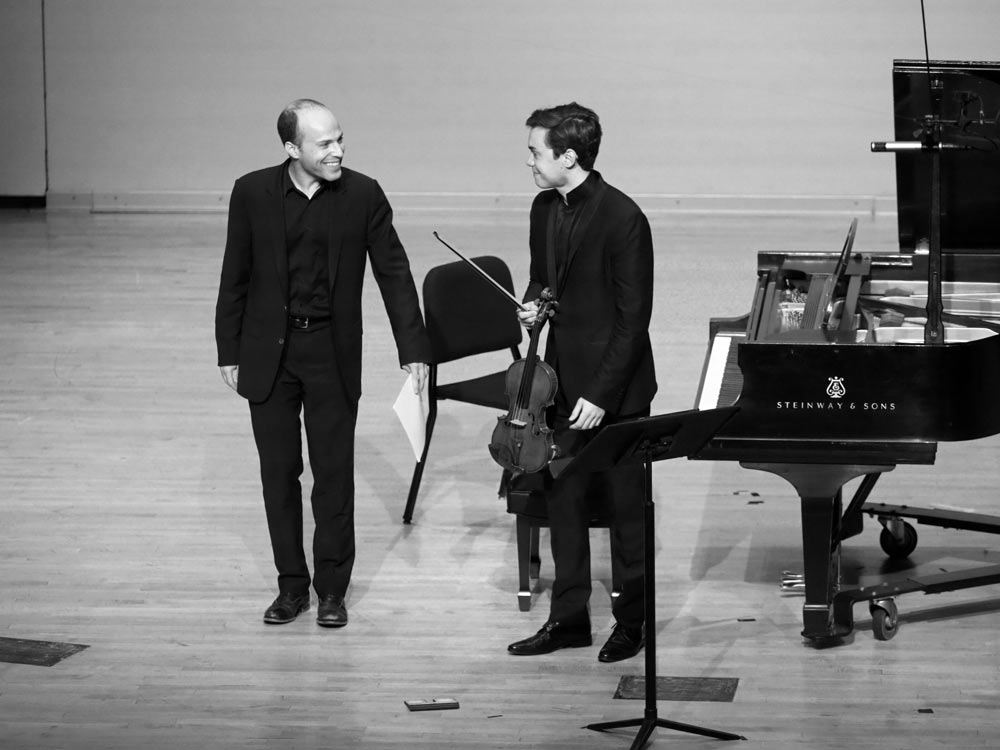 Benjamin Beilman & Orion Weiss standing on stage after performance in black and white