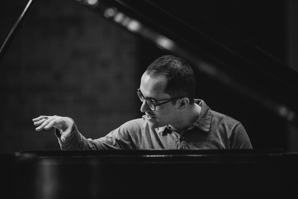 Igor Levit playing piano on stage in black and white