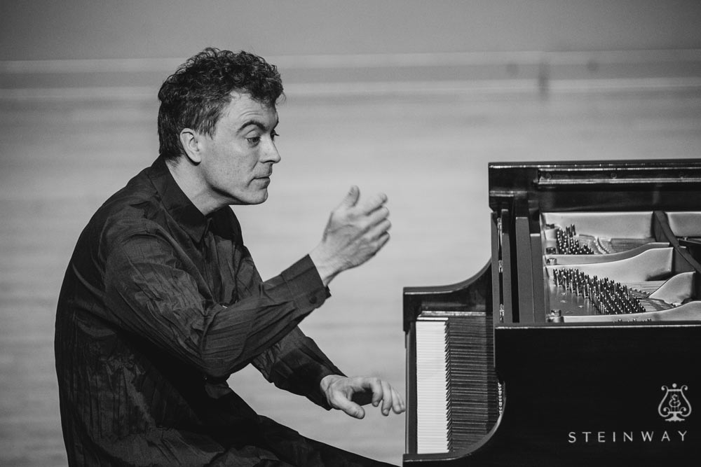 Paul Lewis playing piano on stage in black and white