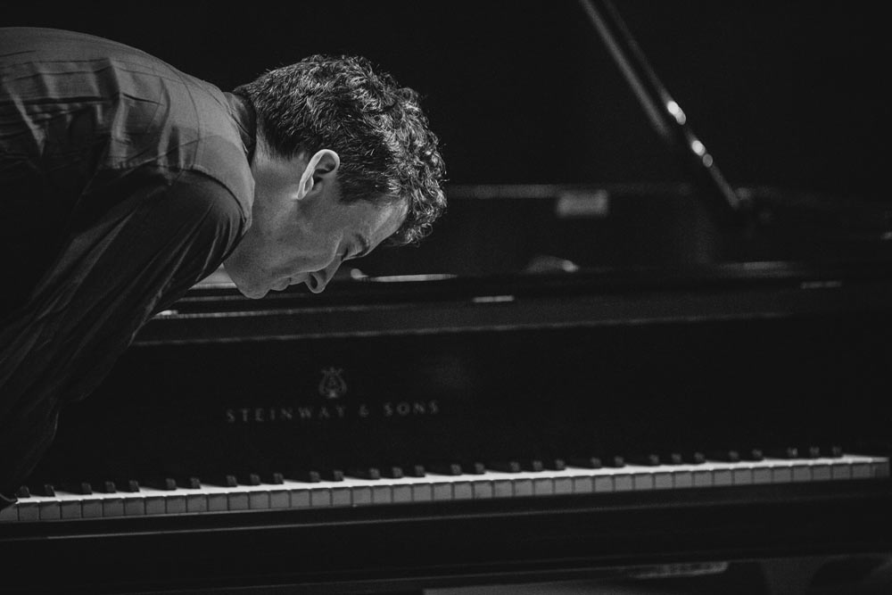 Paul Lewis bowing on stage in black and white