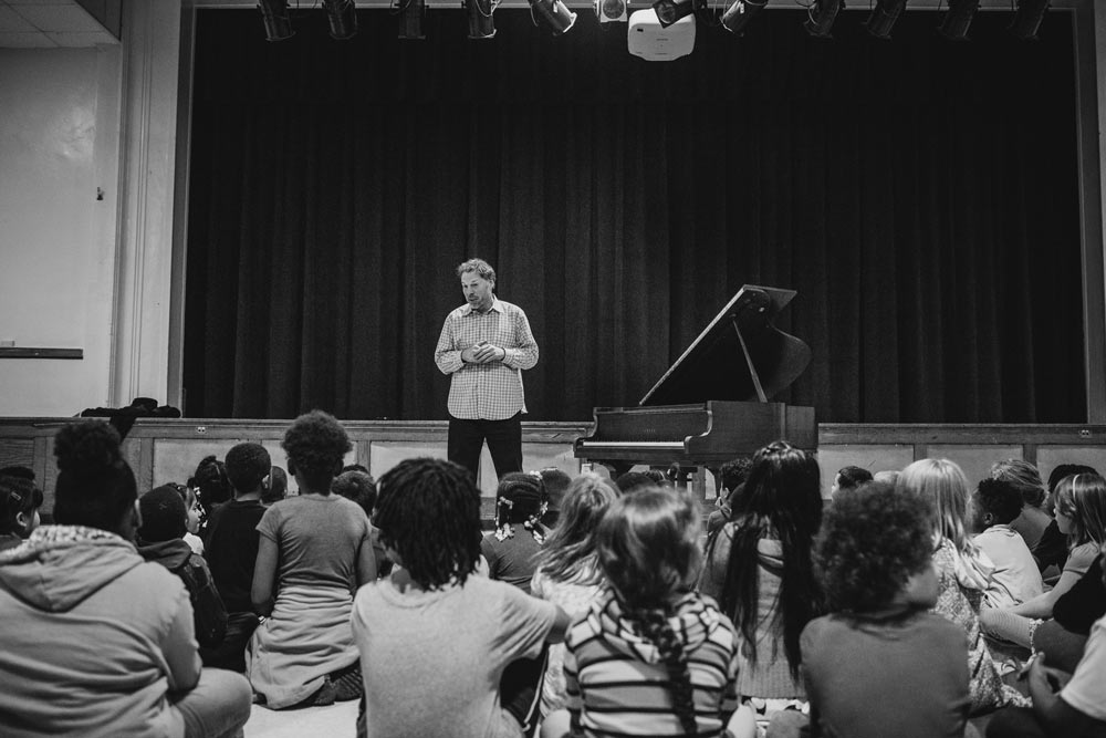 Alon Goldstein speaking to a group of students in black and white