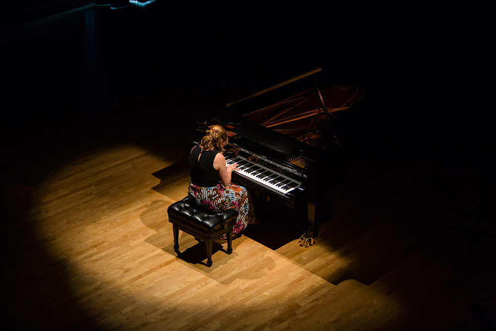 Lori Sims playing piano on stage