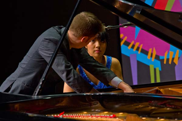 Greg Anderson and Elizabeth Roe looking at each other while playing the piano