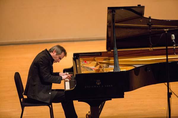 Piotr Anderszewski playing piano on stage