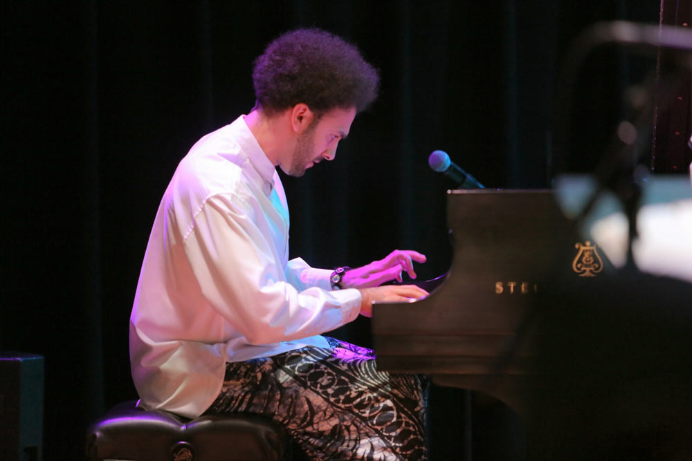 David Virelles playing the piano on stage