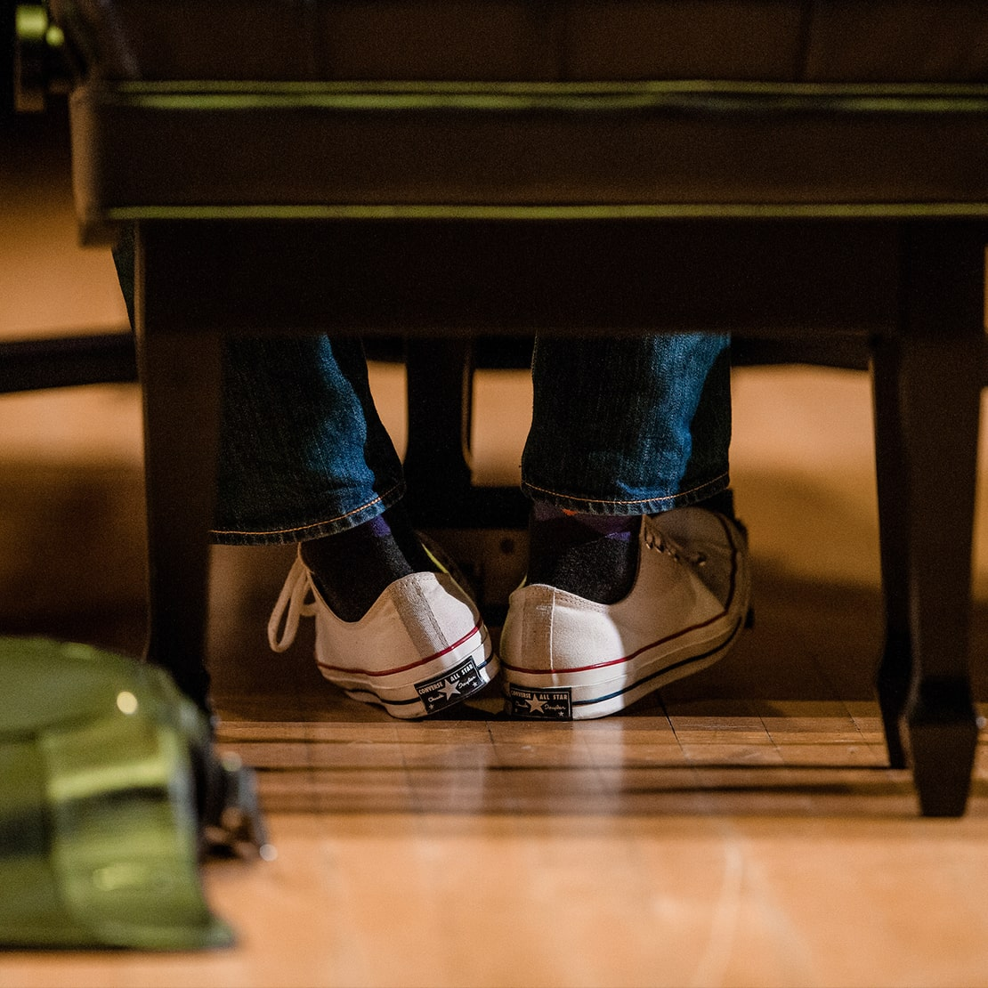 shoes are seen through a piano bench while an artist plays