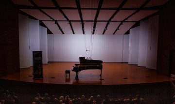 a piano on stage and full audience
