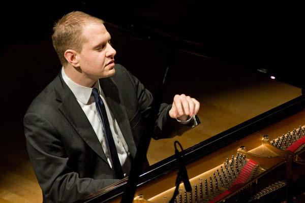 Jeremy Siskind at piano with one hand raised and eyes closed